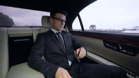 Geschäftsmann, der die schlechten Nachrichten reiten in Luxusauto, erfolglose Investition empfängt stock footage