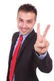 Geschäftsmann, der die Sieggeste zeigt Lizenzfreies Stockfoto
