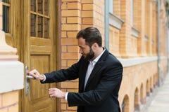 Geschäftsmann, der die Tür eines Gebäudes öffnet Stockfotos