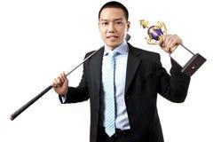 Geschäftsmann, der die Trophäe mit Golfclub anhält Stockbilder