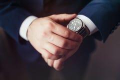 Geschäftsmann, der die Uhr auf seiner Handgelenknahaufnahme schaut Stockbild