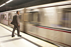 Geschäftsmann, der die Untergrundbahn überwacht, vorbei zu überschreiten Lizenzfreie Stockbilder