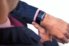 Geschäftsmann, der die Zeit auf seiner Uhr überprüft stockfoto