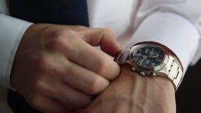 Geschäftsmann, der die Zeit auf seiner Uhr überprüft stock video footage