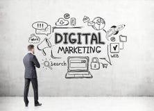 Geschäftsmann, der digitale Marketing-Ikonen betrachtet Stockbild