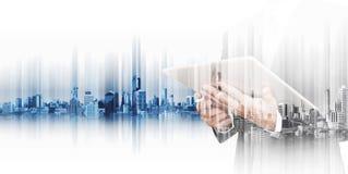 Geschäftsmann, der an digitaler Tablette mit Doppelbelichtungsstadt, Konzepte der Technologiewirtschaftlicher entwicklung arbeite stockbild