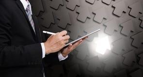 Geschäftsmann, der an digitaler Tablette, mit Pfeilhintergrund mit hellem einzigartigem, Führerschiff im Geschäft darstellend arb Lizenzfreies Stockfoto