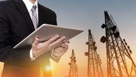 Geschäftsmann, der an digitaler Tablette, mit Satellitenschüsseltelekommunikationsnetz auf Telekommunikationsturm im Sonnenunterg Lizenzfreies Stockbild