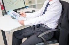 Geschäftsmann, der Dokumente analysiert Stockfotografie