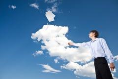 Geschäftsmann, der Dokumente im Himmel wirft Lizenzfreie Stockfotografie