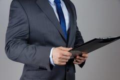 Geschäftsmann, der Dokumente verwahrt Stockfoto