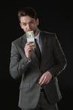 Geschäftsmann, der Dollarbanknoten lokalisiert auf Schwarzem hält Lizenzfreie Stockbilder