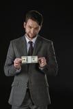 Geschäftsmann, der Dollarbanknoten lokalisiert auf Schwarzem hält Stockbilder