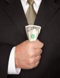Geschäftsmann, der Dollarschein zusammendrückt Stockfotos