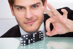 Geschäftsmann, der Domino spielt lizenzfreies stockbild