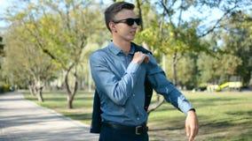 Geschäftsmann, der draußen in den Park überprüft Zeit auf seiner Uhr an einem sonnigen Tag wartet stock video footage