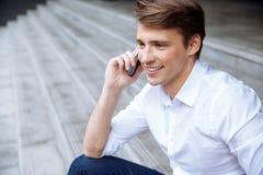 Geschäftsmann, der draußen am Handy sitzt und spricht stockfotografie