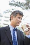 Geschäftsmann, der draußen Kaffee trinkt Lizenzfreies Stockfoto
