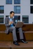Geschäftsmann, der draußen an Laptop arbeitet Stockbild
