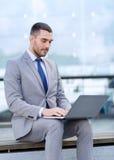 Geschäftsmann, der draußen mit Laptop arbeitet Lizenzfreie Stockbilder