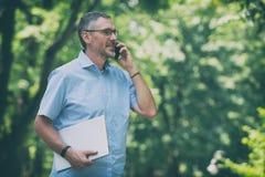 Geschäftsmann, der draußen mit Notizbuch arbeitet stockbild