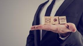 Geschäftsmann, der drei hölzerne Würfel mit Kontaktsymbolen hält Lizenzfreies Stockbild