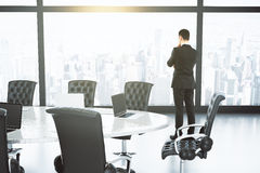 Geschäftsmann, der durch ein Fenster im Konferenzsaal mit schaut Stockfotos