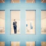 Geschäftsmann, der durch Fenster schaut lizenzfreies stockbild