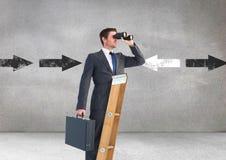 Geschäftsmann, der durch Ferngläser bei der Stellung auf Leiter gegen Richtungspfeile im backgrou schaut Lizenzfreies Stockfoto