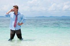 Geschäftsmann, der durch Handy auf dem Strand benennt Lizenzfreie Stockfotos