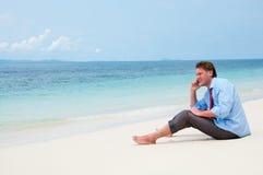 Geschäftsmann, der durch Handy auf dem Strand benennt stockfotografie