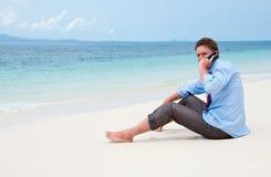 Geschäftsmann, der durch Handy auf dem Strand benennt Stockfotos