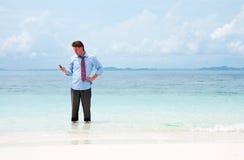 Geschäftsmann, der durch Handy auf dem Strand benennt Stockbilder