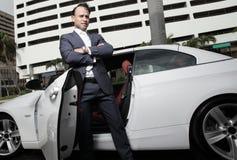 Geschäftsmann, der durch sein Auto aufwirft Stockfotografie