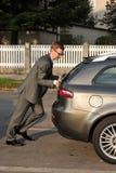 Geschäftsmann, der ein Auto drückt Lizenzfreies Stockbild