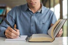 Geschäftsmann, der ein Buch liest und Anmerkungen auf Tabelle schreibt Lizenzfreie Stockfotos
