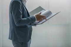 Geschäftsmann, der ein Dokument in der Datei steht und wiederholt Stockfotos