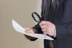 Geschäftsmann, der ein Dokument Lupe durchliest Stockbild
