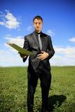 Geschäftsmann, der ein Faltblatt anbietet Stockbilder