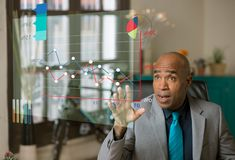 Geschäftsmann, der ein futuristisches Diagramm wiederholt und manipuliert stockfotografie