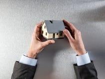 Geschäftsmann, der ein Haus für Hauptbewertung oder Eigentumsverkauf hält Lizenzfreie Stockbilder