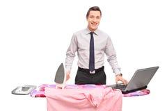 Geschäftsmann, der ein Hemd bügelt und an einem Laptop arbeitet Stockbilder