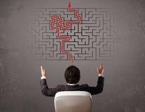 Geschäftsmann, der ein Labyrinth und den Ausweg betrachtet Lizenzfreie Stockbilder