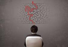 Geschäftsmann, der ein Labyrinth und den Ausweg betrachtet Stockfotos