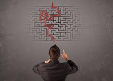 Geschäftsmann, der ein Labyrinth und den Ausweg betrachtet Stockbilder