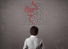 Geschäftsmann, der ein Labyrinth und den Ausweg betrachtet Stockfoto