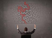 Geschäftsmann, der ein Labyrinth und den Ausweg betrachtet Lizenzfreie Stockfotos