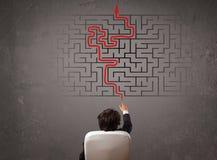 Geschäftsmann, der ein Labyrinth und den Ausweg betrachtet Lizenzfreies Stockbild