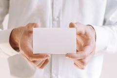 Geschäftsmann, der ein leeres Blatt Papier zeigt Geschäftsmann im weißen Hemd, das Visitenkarte gibt stockfotografie