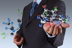 Geschäftsmann, der ein Molekül hält Stockfotos